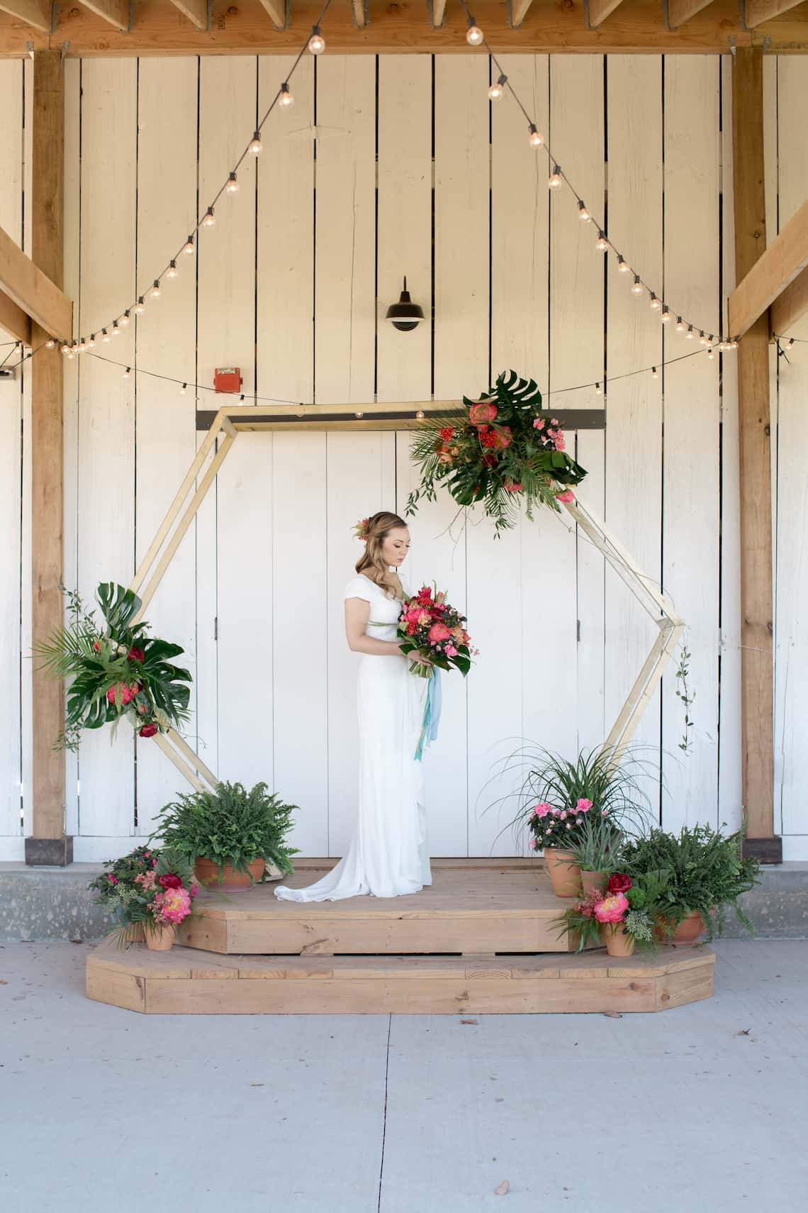 Bride with Bouquet Standing Underneath Hexagon Arch with Tropical Flowers
