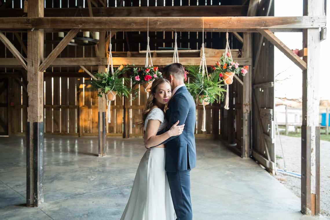 Bride Standing with Groom in Front of Hanging Teracotta Plants