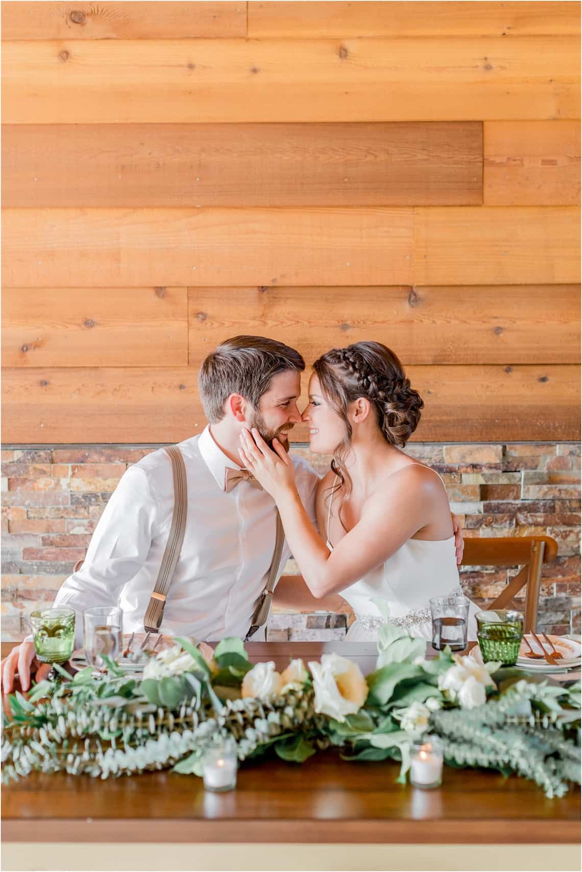 Bride and Groom Sitting at Farm Table