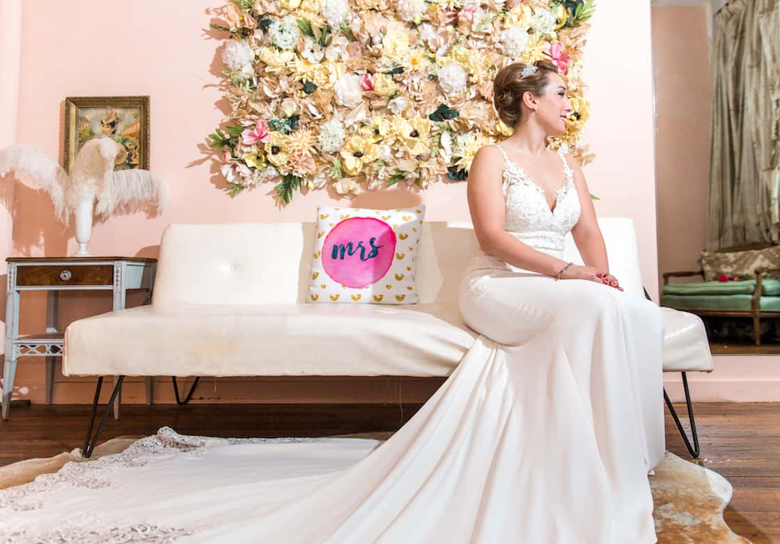 Bride Sitting in front of Wall of Flowers