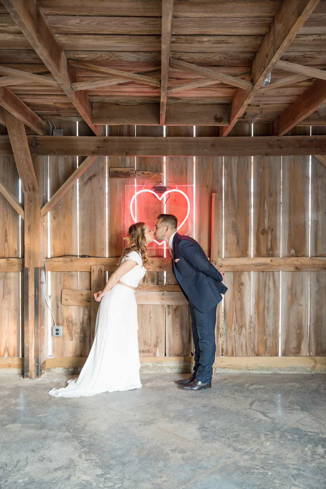 Bride and Groom Kissing in Front of Neon Heart Sign