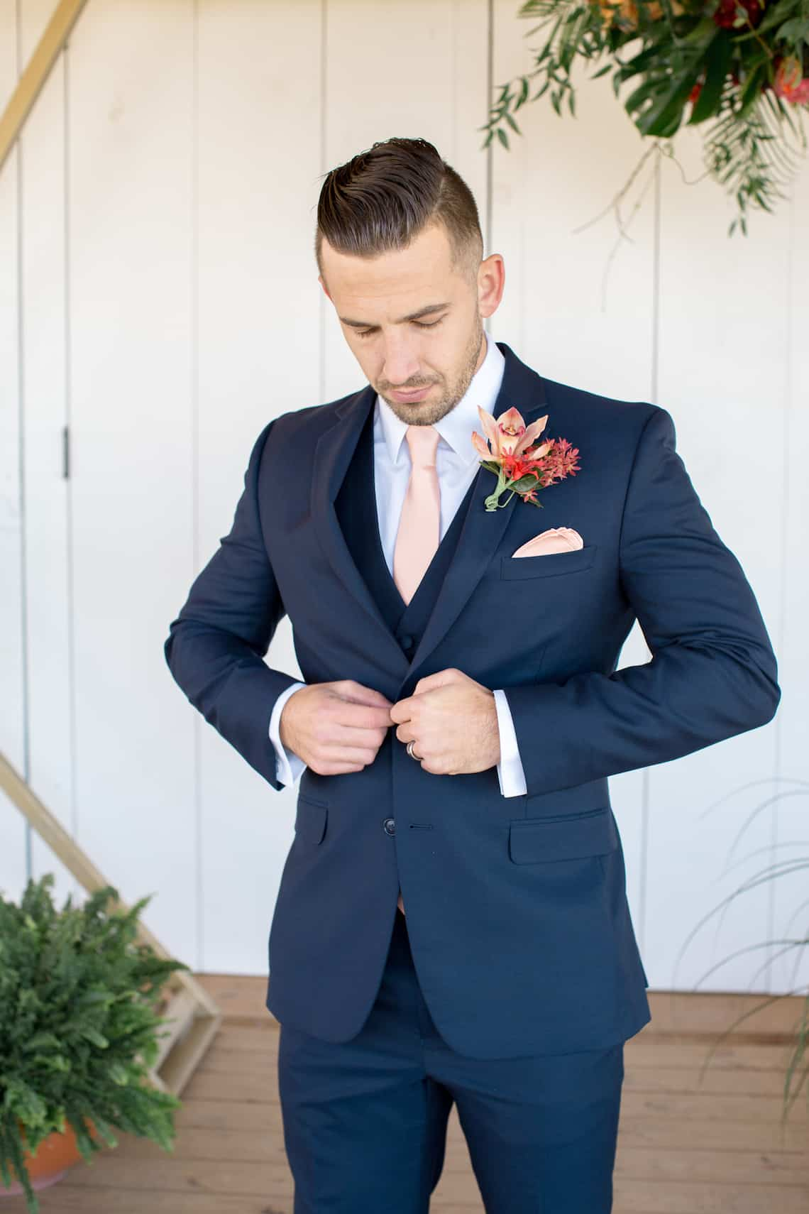 Groom Buttoning Navy Suit with Pastel Orange Tie