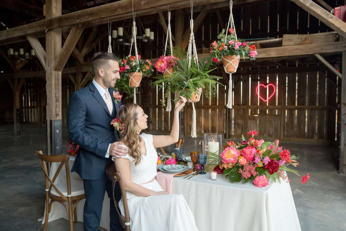 Newlyweds Sitting at Tropically Designed Farm Table with Neon Heart Sign