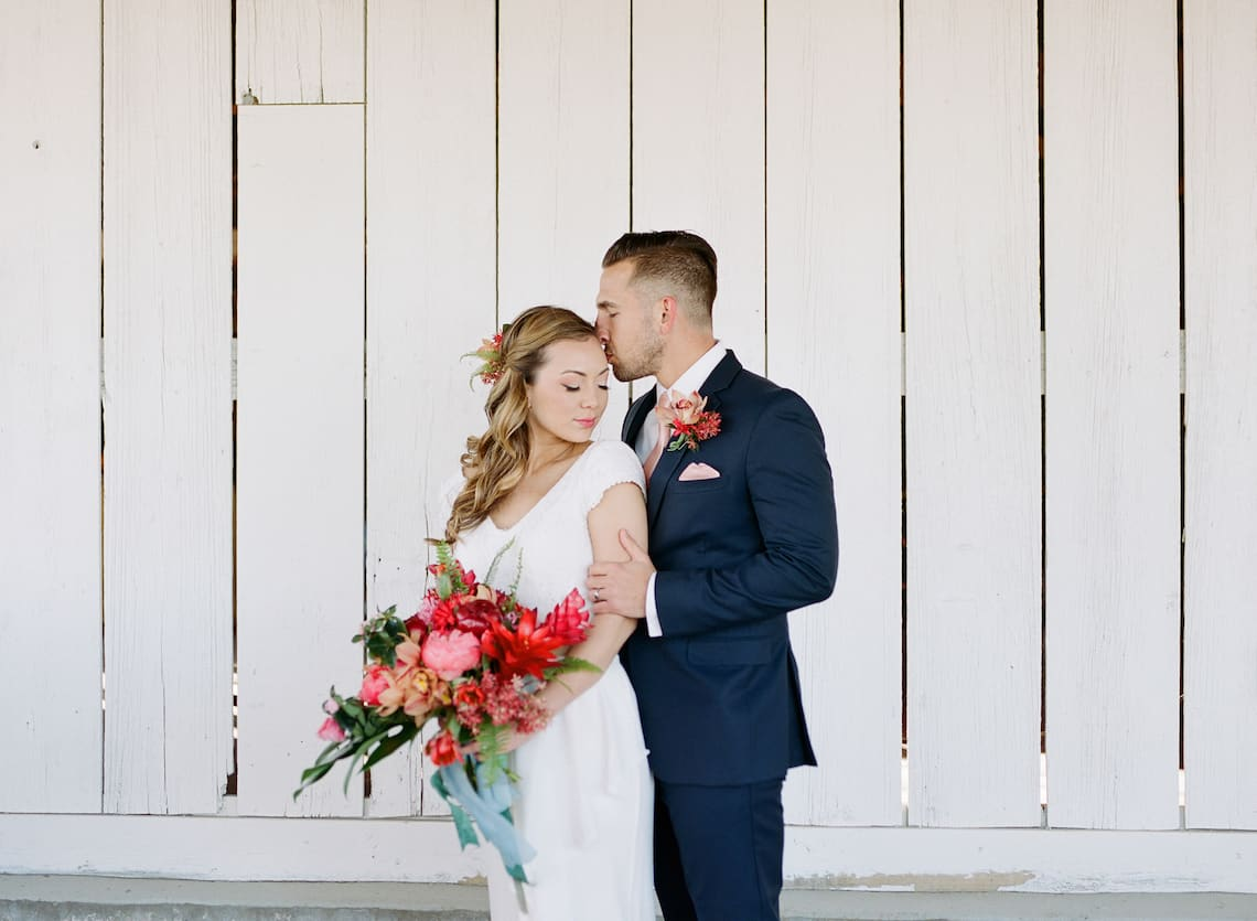 Groom Kissing Bride with Tropical Flowers