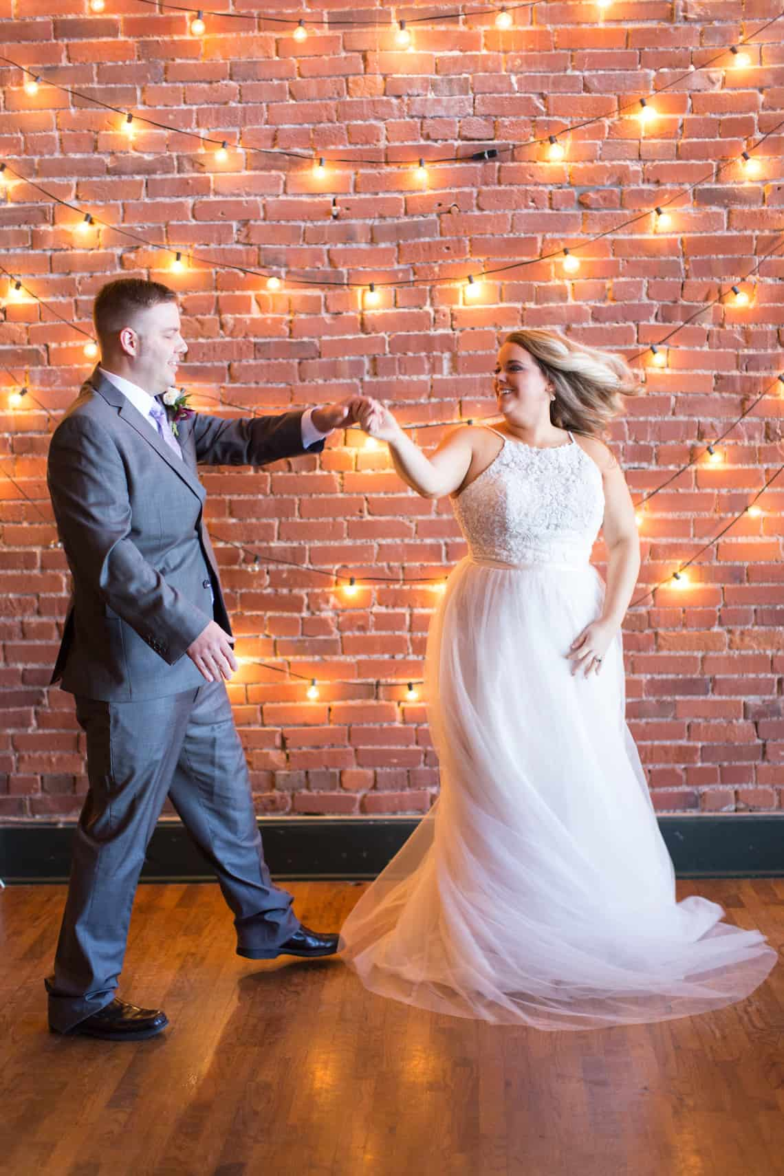 Bride and Groom Dancing in Front of Edison Bulbs