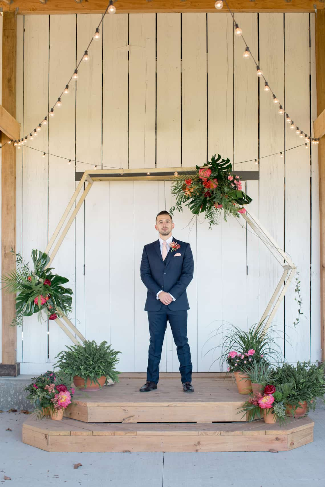 Groom in Navy Suit Standing in a Hexagon Alter with Tropical Flowers