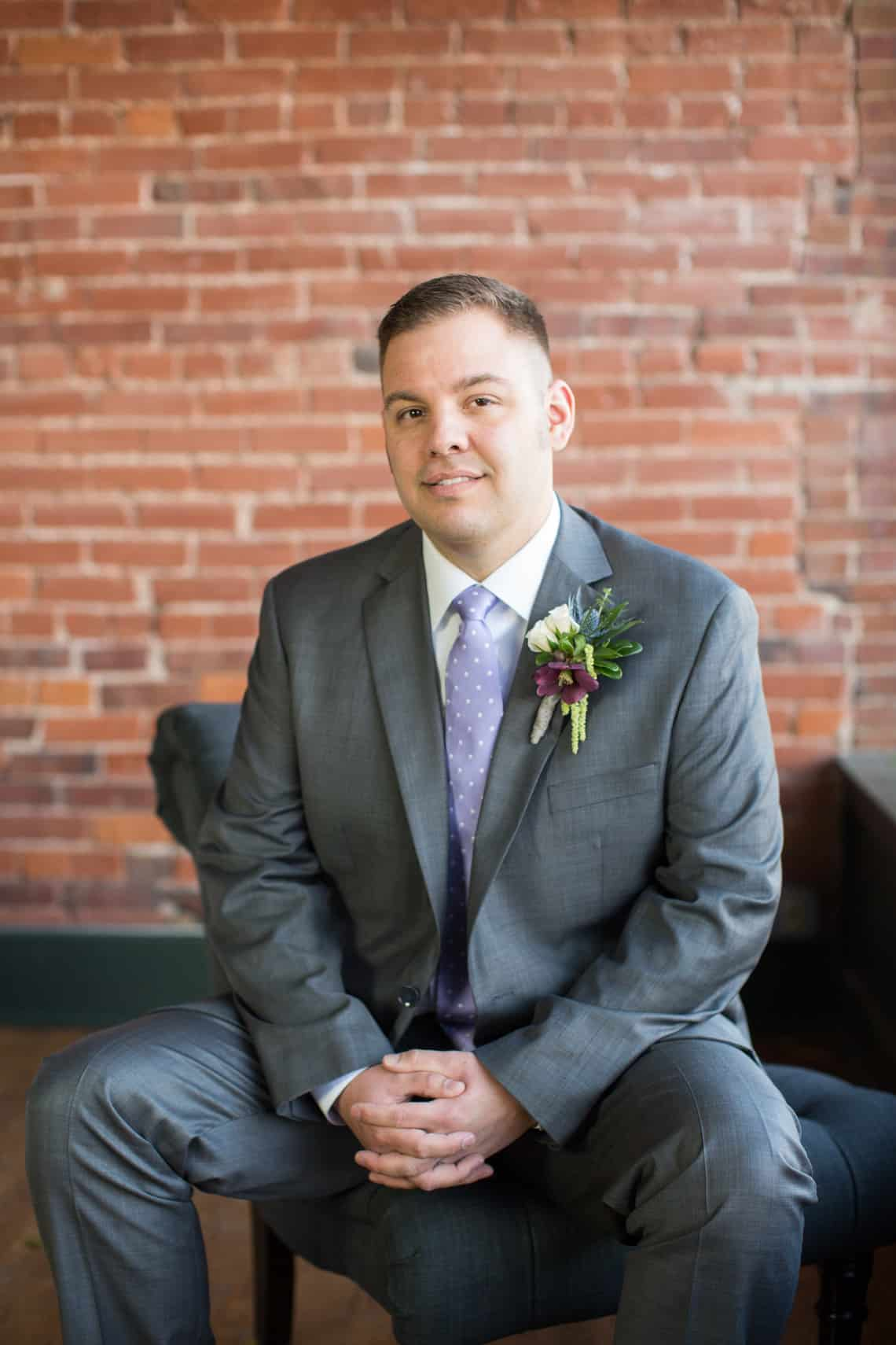 Groom Sitting in Grey Tux with Modern Boutonniere