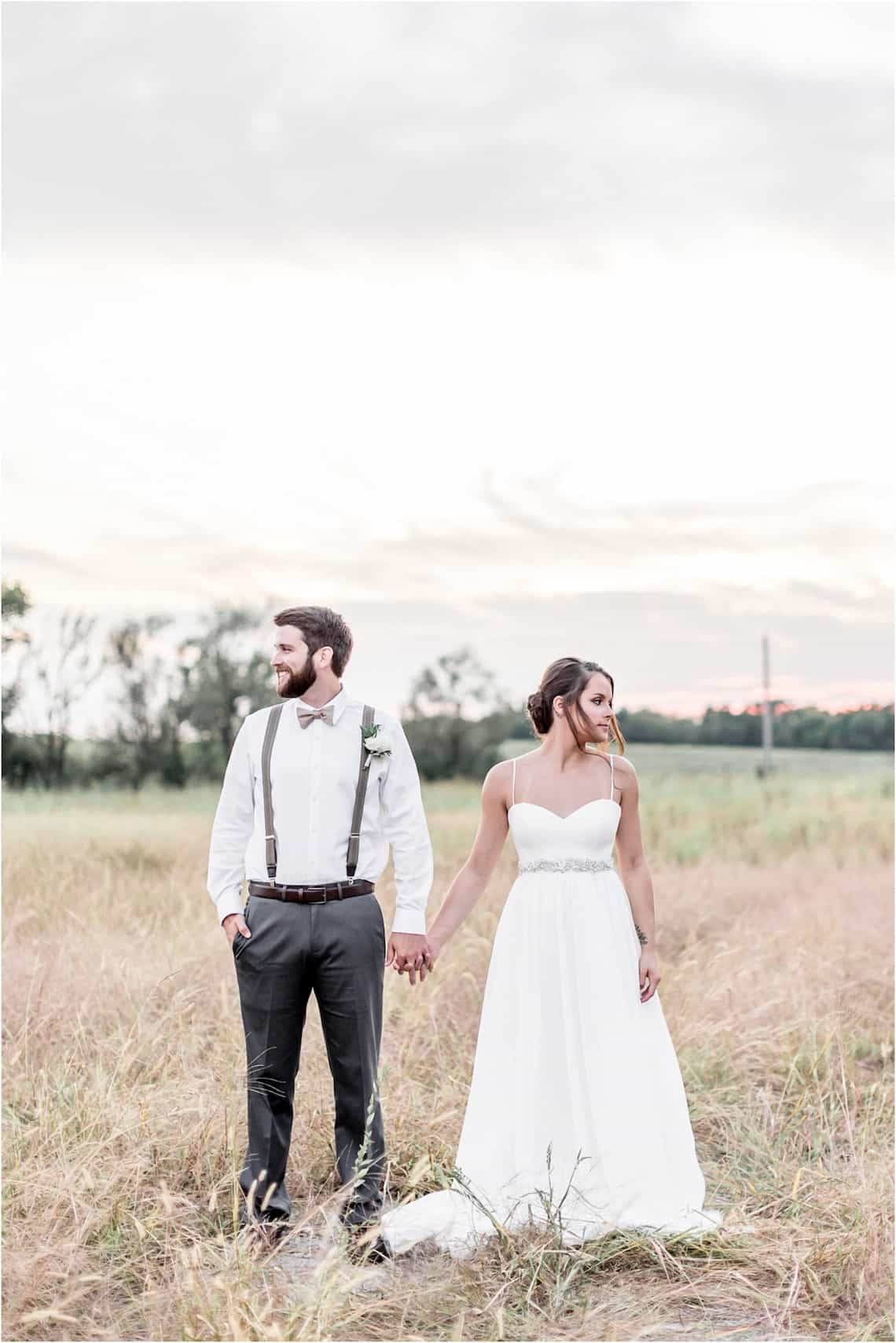 Bride and Groom Looking Away in Middle of Field