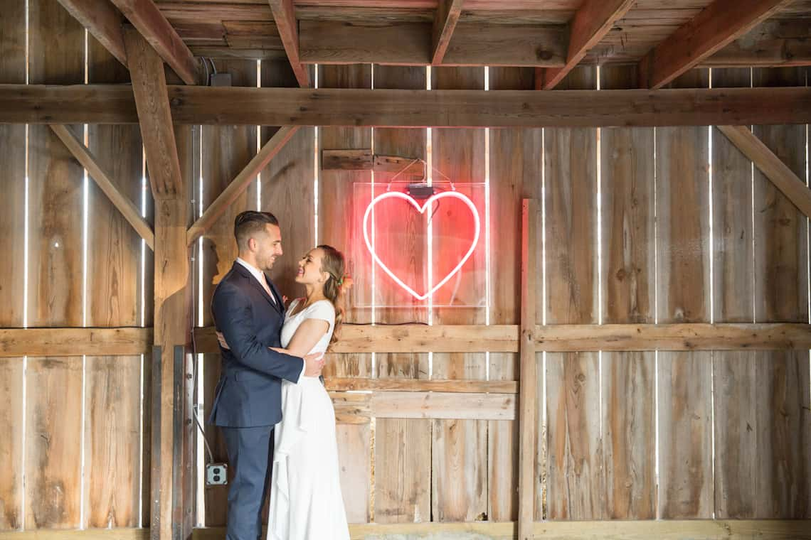 Bride and Groom Standing by a Neon Heart
