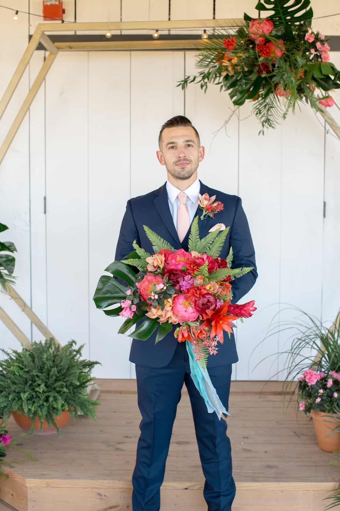 Groom in Navy Suit Holding Tropical Boutonniere