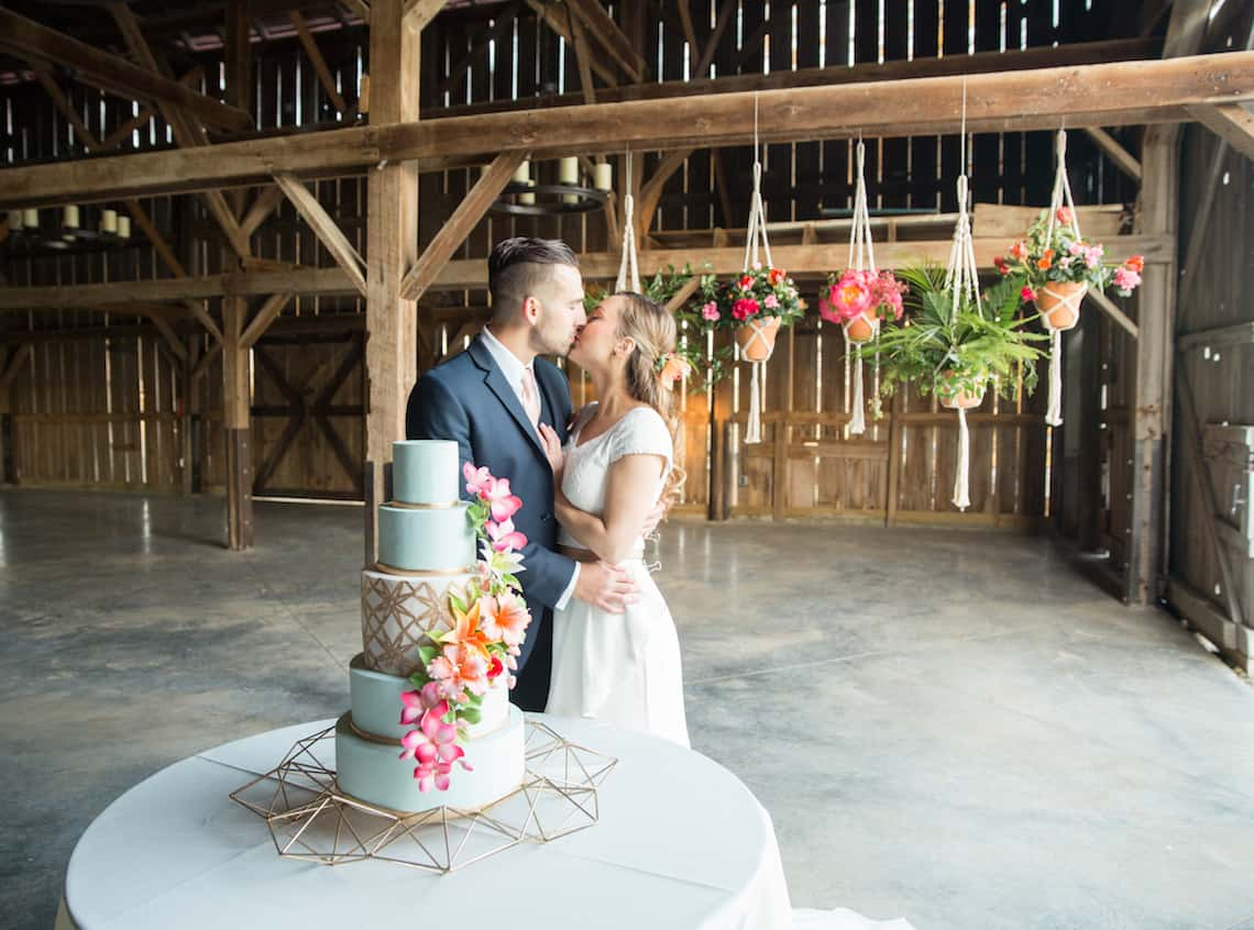 Bride and Groom Kissing at Light Blue Wedding Cake