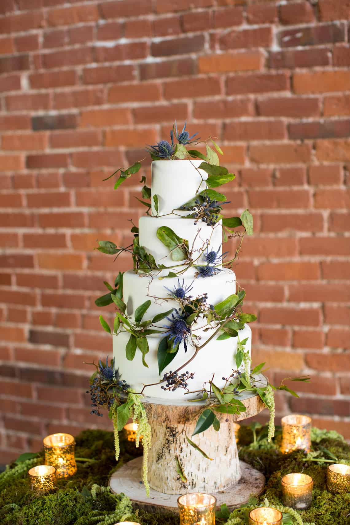 White Wedding Cake with Greenery Accents and Gold Candles