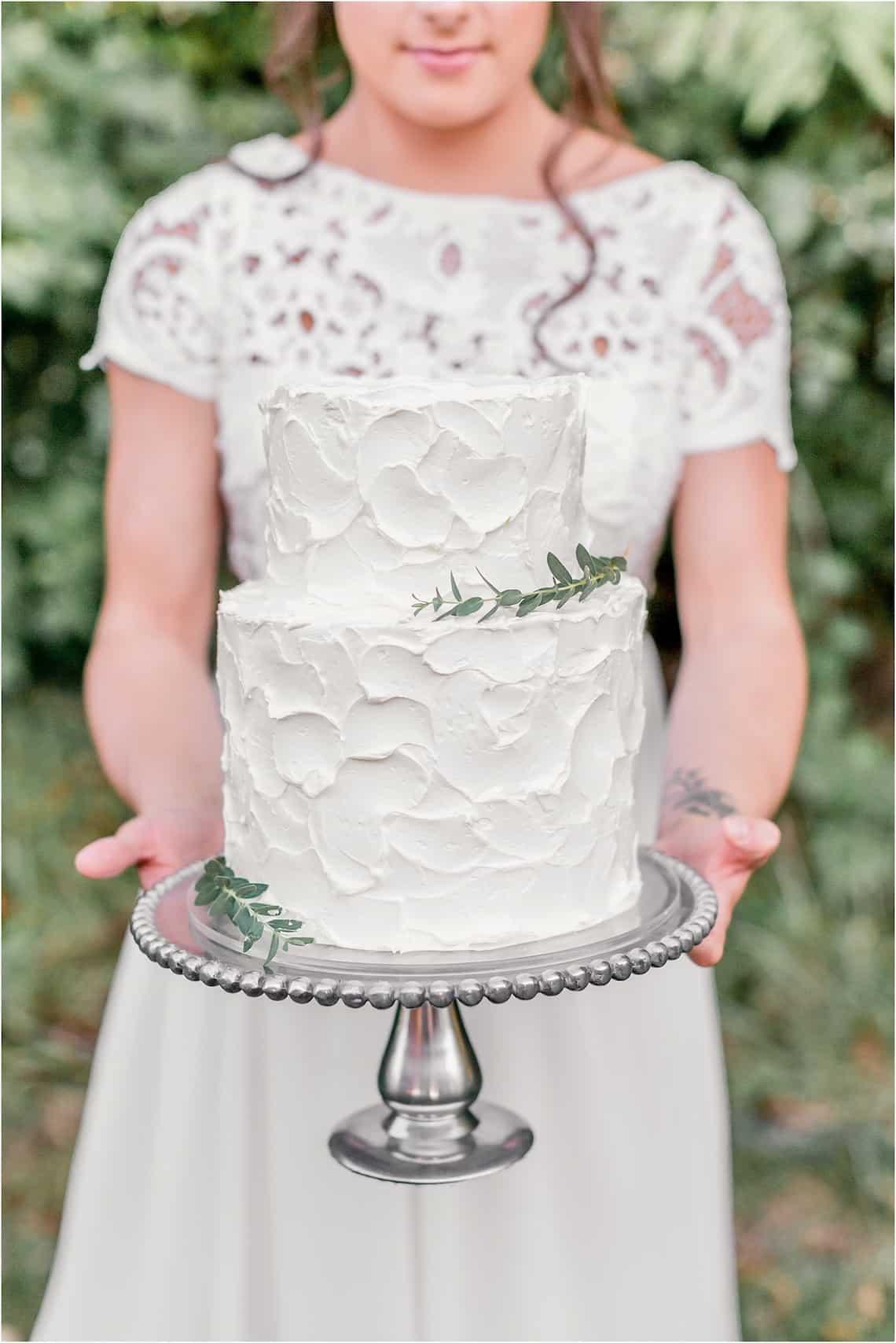 Bride Holding Classic White Wedding Cake