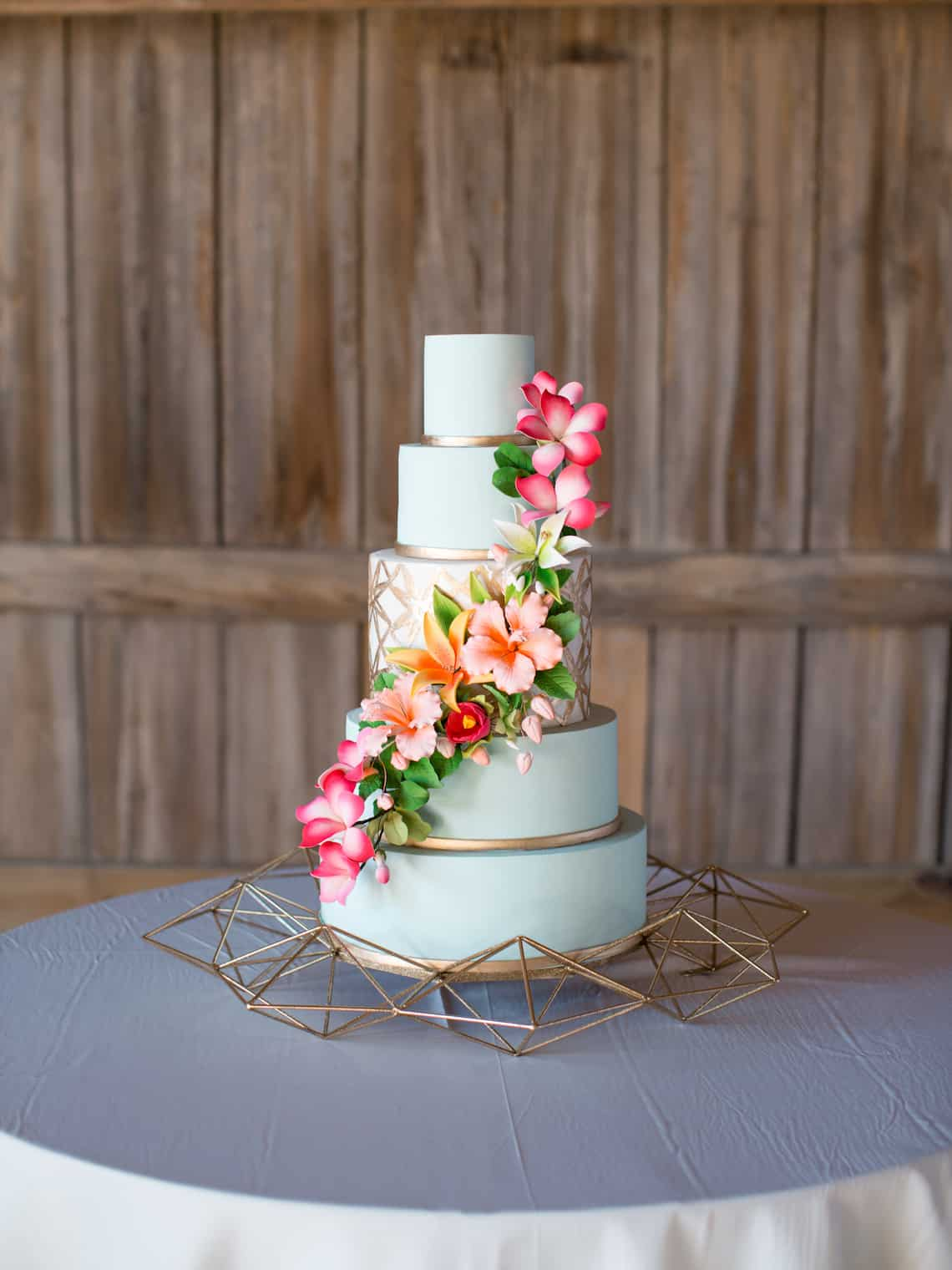 Light Blue Wedding Cake with Tropical Flowers and Gold Geometric Designs