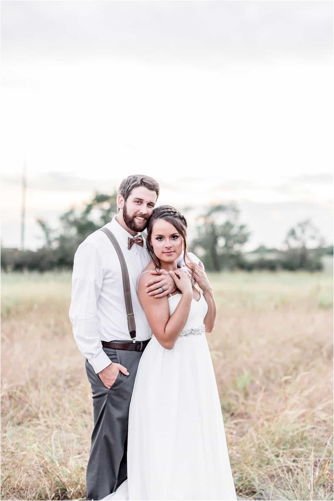 Snuggling Bride and Groom Standing in Field