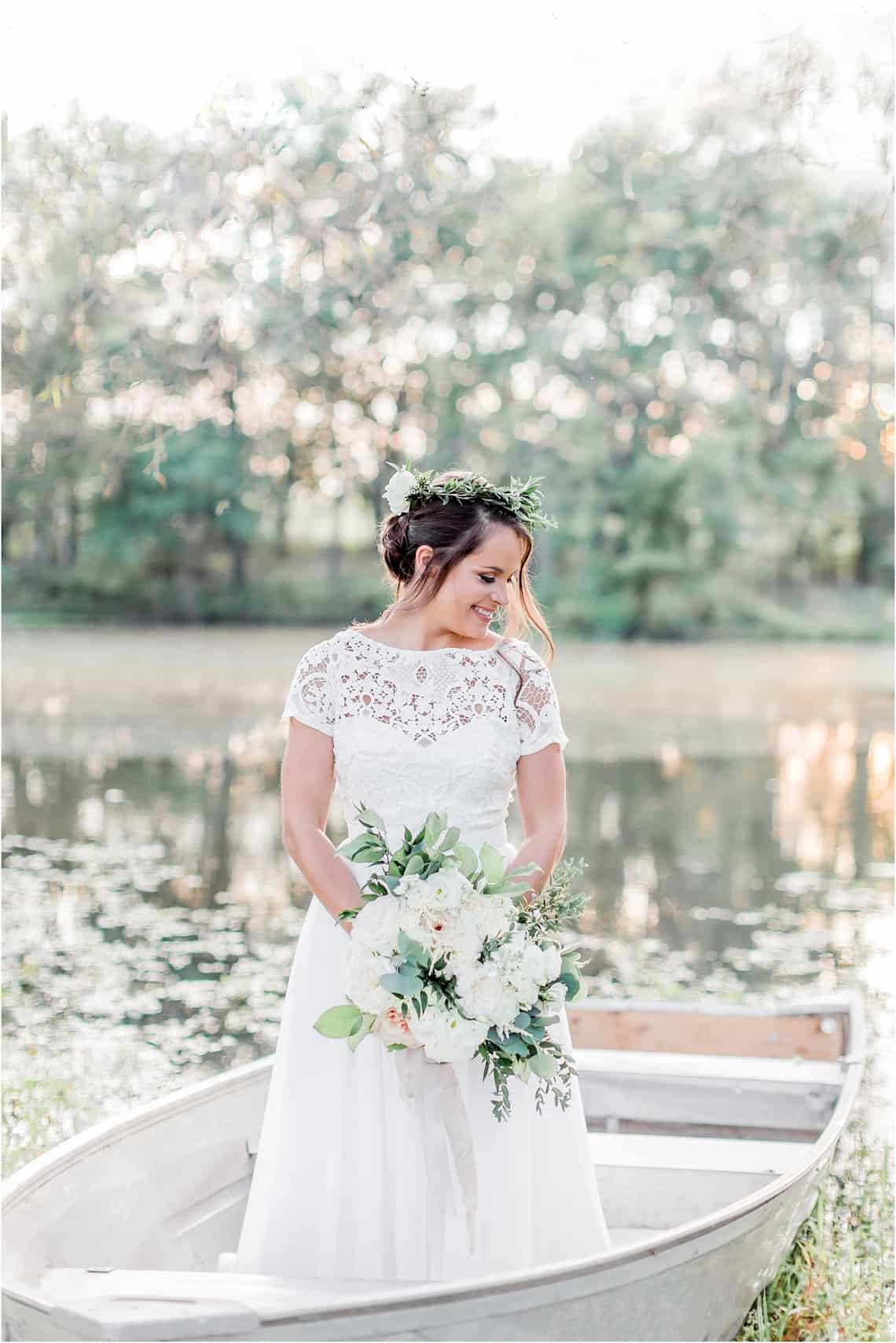 Bride Standing in Boat on Lake with White Flower Bouquet
