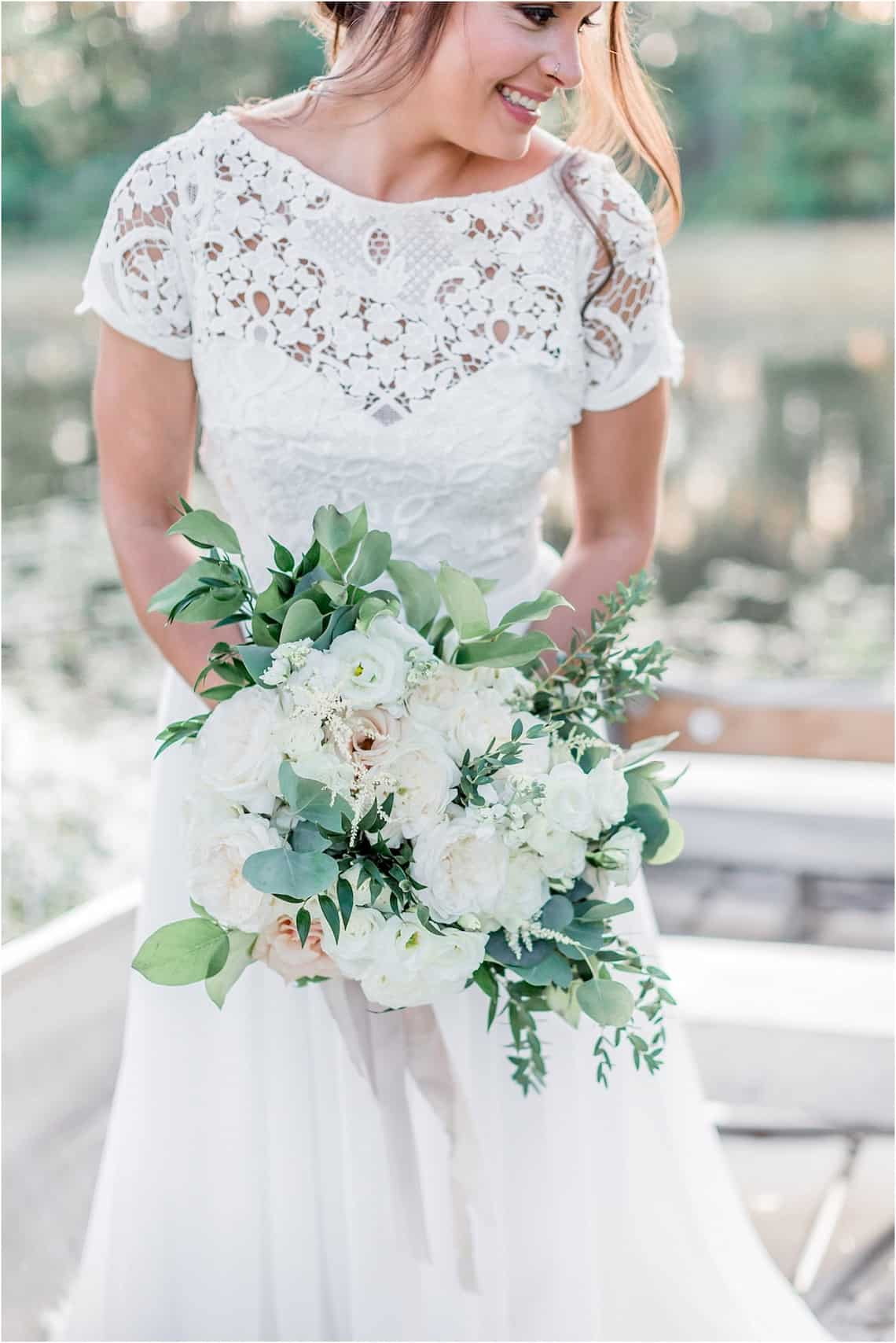 Smiling Bride Standing in Boat on the Lake with White Flowers and Greenery Bouquet