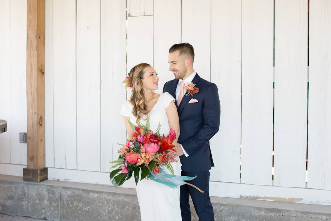 Bride and Groom Smiling at Each other with Tropical Bouquet