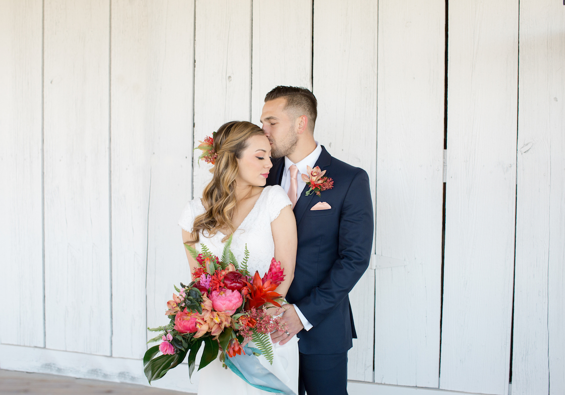 Groom Kissing Bride on the Head with Tropical Bouquet
